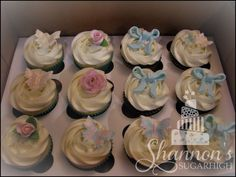 Cupcakes with fondant butterfly, flower, and bow accents in theme colours of aqua, pink, gold, and white.