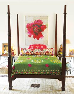 Ireland's new color-saturated fabrics pack a punch. In a guest bedroom: The bedspread and pillowcase with suns are from her latest collection. The bolster pillow is made from an antique suzani. Flower photo by Oberto Gili, from Nathan Turner.   - HouseBeautiful.com