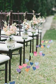 Decoração de cadeiras com flores em vidro e gramado com corações de papel espetados com palitos