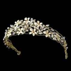 "Perfectly lovely, this adjustable tiara features gold flower details and rhinestones woven into a lacy gold plated backdrop. This piece is perfect for the bride, bridesmaid, or flower girl. The design stretches throughout the piece, measuring 9-1/2"" wide and 1-1/2"" tall, and ending in two loops that allow you to fasten the piece in your hair with bobby pins.  Size: 9 1/2"" wide and 1 1/2"" tall"