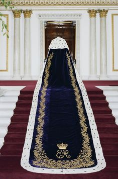 Coronation robe of deep purple silk velvet, edged with ermine and embroidered in gold thread with crowned E II R monogram and ears of wheat, worn by Queen Elizabeth II in Made by Ede & Ravenscroft, London, Royal Collection Trust.