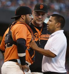 San Francisco Giants manager Bruce Bochy, center, and a trainer check on the condition of catcher Hector Sanchez, left, in the second inning of a baseball game against the Los Angeles Dodgers on Friday, July 25, 2014, in San Francisco. Sanchez did not return to the game in the third inning. (AP Photo)