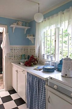 Blue and white in a kitchen is always so charming.  I would certainly not mind standing at this sink and doing the dishes.