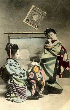 Hangyoku with a Large Doll and Chin Dog 1906. Two Hangyoku (Young Geisha), one adjusting the clothes of a large Ichimatsu Ningyo (Play Doll) and another holding a toy Japanese Chin Dog wearing a traditional Maedare (bib).