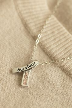 """Wear our pink ribbon necklace as a symbol of all that you have overcome. The shining ribbon pendant contains sparkling pink cubic zirconia stones and the word """"survivor"""" displayed proudly across the front."""