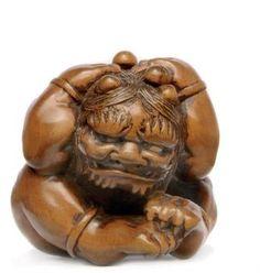 A Wood Netsuke Signed Masanao, Edo Period (19th century) Of a Setsubun oni cowering from beans, Yamada School 3.9cm. long