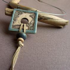 Keramický náhrdelník NATURA (59) Originální keramický náhrdelník z kolekce NATURA. Každý kus je originál. Průměr obruči: cca 14,5 cm Délka přívěsku: cca 11 cm Velikost placičky: 3,5 x 3,5 cm