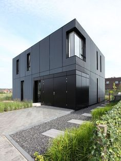 Black metal siding on the exterior of this home gives the cubic house an even more modern appearance and contrasts the greenery surrounding it.