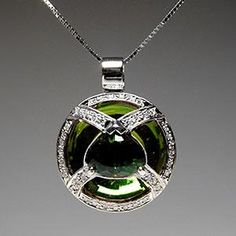 Only the middle teardrop is a green gem (tourmaline)... the outside green comes from the parabola design that reflects the color. Pretty cool.