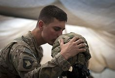 U.S. Army Spc. Brit B. Jacobs, a combat medic from Sarasota, Fla. gives a farewell kiss to the helmet of one of his fallen comrades.