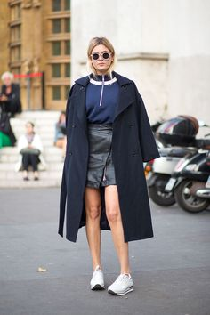 Here we see a long coat being used as a cape, matched with a short leather skirt and topped off with running shoes.