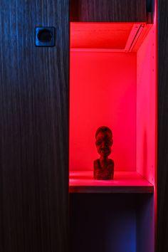 Red background on figurine in closet by Roy Rozanski, via 500px
