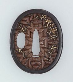 Tsuba with design of clematis on a simulated woven background. Japanese, Edo period, early to mid-19th century.