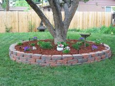 Surround trees with mulch, small plants, and brick - cheap, and prevents tripping and mowing accidents!
