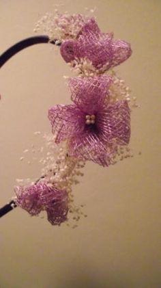 Diadema forrada de algodón color violeta con flores de sinamay color lila con pistilos marfil y bolitas de flor seca en  marfil.