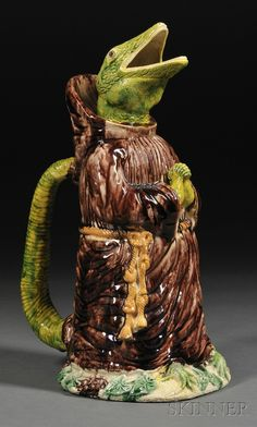 Anthropomorphic Majolica Pitcher Modeled as a Lizard in Monk's Robes, c. 1900, with the mouth as the spout and the handle formed by the tail, impressed mark on base.