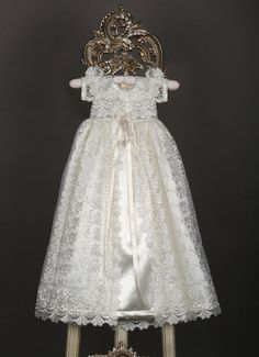 This off white gown is made with a beautiful lace overlay and satin underneath. A beautiful bow at the center of the waist accentuates the dress. - Christening Gown for baby girls - Off White Lace Ove