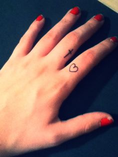 A cross and a heart on fingers