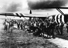 Parachutistes contrôlant équipements et armements avant de monter dans les planeurs Horsa ceints des bandes noires et blanches de reconnaissance D-Day.