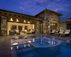 The stone exterior and curved tile rooftop show the Spanish influence in this modern interpretation of Spanish style.