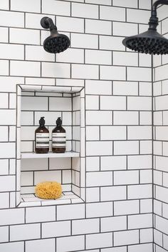 Fantastic walk-in shower features walls clad in white subway tiles finished with black grout lined with a tiled shower niche and oil rubbed bronze shower heads.