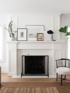 Classic wood mantel painted white and decorated by stacking/overlapping several pieces of art. We love the elegant, linear lines...and that chair?! So much love for this living room vignette.