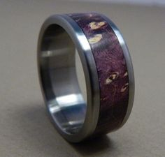 This titanium ring is handmade and inlayed with a gorgeous piece of purple box elder burl wood. We really love the way this wood works up - its a
