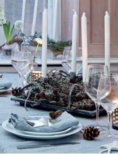 I spisestuen er julebordet i år dækket op i hvidt og sølv – sart og fint som den første frost. På servietterne ligger stjerneformede spejle, som Signe har skrevet navn på og brugt til bordkort. På bordet ligger grankviste, kogler og små hvide ballerinaer, som Signe har haft i mange år. Spejlstjernerne er fra Tine K Home, mens dug og servietter er fra Society.