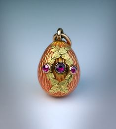 A Faberge Gold, Enamel and Ruby Egg made in St. Petersburg between 1899 and 1901.  The egg is covered with a salmon pink guilloche enamel.  The front is centered with a bezel-set round faceted ruby flanked by two overlapping chased green gold garlands, each set with a small ruby.  The detachable gold fitting is marked on the suspension ring with 56 zolotnik standard (14K), with initials of St. Petersburg assay master Yakov Liapunov and workmaster's initials ' E K ' for Erik Kollin.