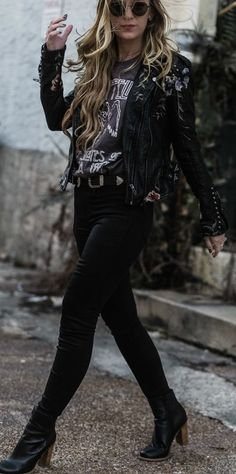 Cute edgy concert outfit styled with embroidered and studded leather jacket, coated jeans, and band tee