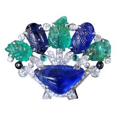 CARTIER Art Deco 'Tutti Frutti' Rare Vase Flower Brooch Probably USA circa 1925 Beautiful flower and vase brooch set with a large carved sapphire within a diamond surround with 'flowers' in carved sapphire and emeralds with onyx and black enamel highlights Cartier, circa 1925