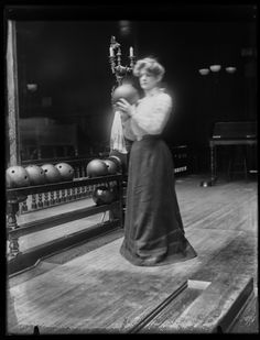 Women bowling in the year 1900. I find it fascinating to see how dark it is in the bowling alley, and look at that candelabra there over her shoulder.  So cool.