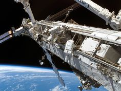 Astronauts perform external repairs on space station.