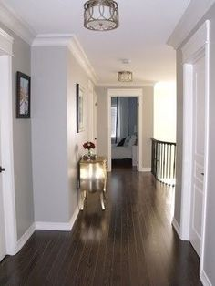 -Wall color =  Benjamin Moores Revere Pewter HC-172, this is one perfect hallway - dark floors, grey and white trim; will have to keep this color in mind