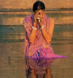 Woman doing Hindu ritual in the Ganges River. At the beginning of every day, devout Indians make offerings including flowers and food, with some people releasing oil lamps and lanterns into the Ganges.