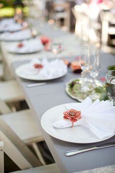 White fanned napkins are bound by charming pink flowers for a pop of color.