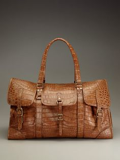 * Large weekender bag * Alligator with double top handles and detachable shoulder strap * Flap opening with magnetic and buckle strap closure * Nylon interior with three slip pockets and zip pocket * Body length 21 inches; height 15 inches; width 8 inches * Drop handle 10 inches; shoulder strap drop 25 inches Brand:Burberry Prorsum Color:tan Material:Alligator Origin: Italy