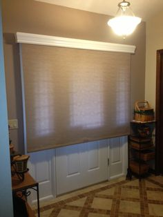 Beautiful neutral, cordless roller shade from @Horizons Window Fashions with a painted wooden cornice from Graber. Great way to provide privacy over door window and sidelights. | ShadesToYou
