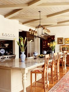 A decorative ceiling treatment, light palette, and colorful artwork create a warm interior scheme in this attractive and functional kitchen. An island with a polished-granite countertop measuring 5 by 15 feet extends down the center of the kitchen. A butler's pantry with sliding barn doors and a rolling library ladder allows some prep work to take place behind the scenes. (Photo: Photo: Robbie Caponetto; Designer: Pursley-Veltman architects)