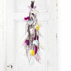 Färgglatt påskris på dörren. Ägg och fjädrar.