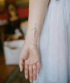 Elegant floral wrist tattoo by Nando