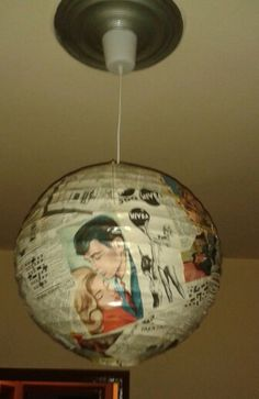Handmade hanging paper light from ikea covered with old magazines.