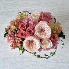 胸がキュンとするような春の訪れ。桜の木を見上げると、大きく膨らんだ、たくさんの蕾。今か今かと春への期待が高鳴ります。桜は、開花を待つときも、咲き始めも満開の頃も、花びらの舞う様も、どれをとっても素敵ですね。スリジエ・アン・フルールとは、フランス語で「桜」を意味する言葉。小花の模様のオーバル型の器に、桜をイメージした花たちを集めました。ふっくらとした咲き姿がロマンチックな、プリザーブドフラワーのオールドローズ。花びらのグラデーションもステキです。結婚式でのご両家様へのプレゼント大切な方へ、お祝いや感謝の気持を込めての贈り物母の日や敬老の日、ご自宅用としてもお楽しみいただきたいアレンジメントです。クリアケースに入れてラッピングをしてお届けします。メッセージカードをご希望の方は、ご注文の際、備考欄にお書き添え下さい。メッセージカードは名刺サイズです。また、メッセージをご自身で書かれる場合は、白紙のものを同梱します。【cerisier en…