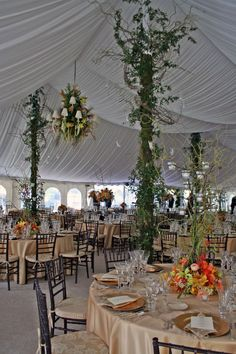 Decorating poles to your reception tent will make it feel less like a tent. Designs by McNamara Florist