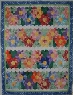 Not Gramma's Flower Garden ~ make rectangles from two pieces that are cut with a 60 degree slant in the middle. Some of the cuts go one way, and some are reversed.