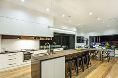 Large open concept living area and kitchen. Kitchen incorporates modern white cabinetry with natural wood island which includes a sink and cabinets