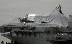 The space shuttle Enterprise is draped with torn fabric that had protected it before Sandy passed though, leaving the spacecraft shrouded on the deck of the Intrepid Sea, Air & Space Museum, on the Hudson River in New York