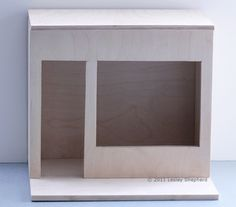 Unfinished dollhouse scale windowbox with a shop front.