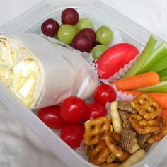 all-american bento: The sandwich roll is filled with Deviled Egg Salad and wrapped with waxed paper. The other munchies are cereal mix, grape tomatoes, baby carrots and celery sticks, waxed wrapped cheese and red & green grapes.