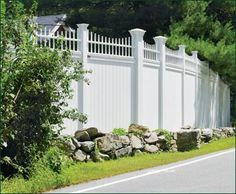 Vinyl Universal Board Fence - A Board fence that affords privacy and security can also impress with its stateliness and style. This 7' high gently curving curbside Universal has convex 2' Cambridge spindle topper.